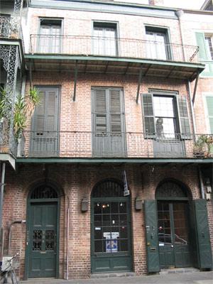 Foto da casa em New Orleans, com uma mulher olhando pela janela