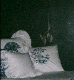 Foto de alguns travesseiros na penumbra e a imagem de uma pessoa aparece atrás deles.
